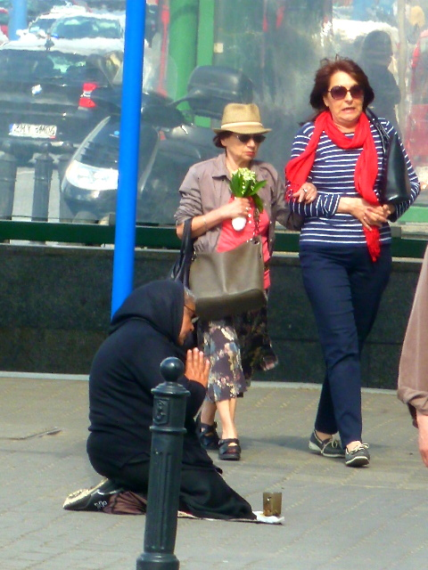 In Warsaw, Poland, a woman on her knees, praying that her begging will pay off?